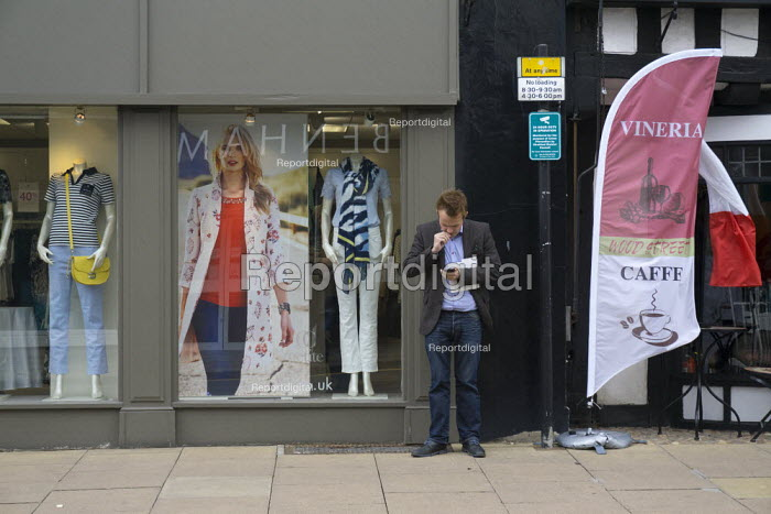 A stressed man using his mobile outside a shop, Stratford Upon Avon, Warwickshire - John Harris - 2015-06-02