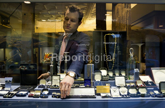 An assistant selecting jewellery for a customer from the window display of a prestige jewellers, Stratford Upon Avon, Warwickshire - John Harris - 2015-06-02