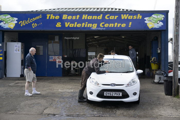 A car owner looks on as migrant workers wash his car at The Best Hand Car Wash and Valeting Centre, Stratford-upon-Avon, Warwickshire - John Harris - 2015-06-09
