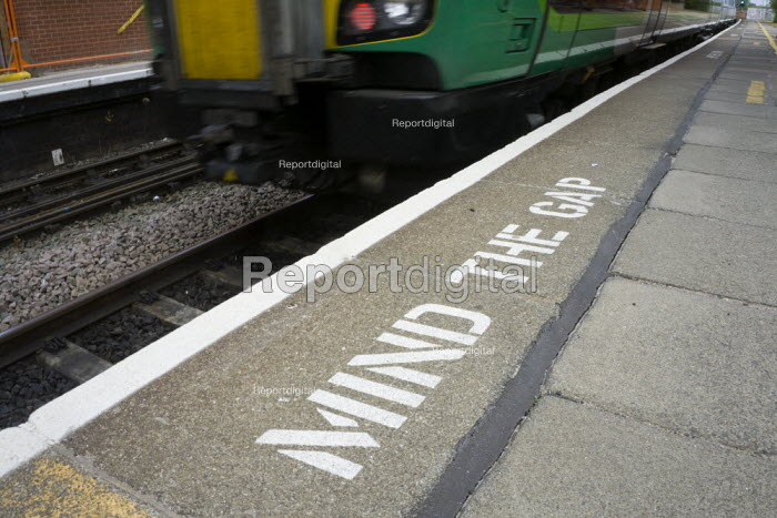 Mind the gap warning on the railway station platform as a train departs, London and Midland line, Stratford-upon-Avon, Warwickshire - John Harris - 2015-06-10