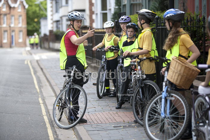 Bikeability instructor instructing pupils on a Cycle Proficiency training course on the roads around Broad Street, Stratford-upon-Avon Primary School, Warwickshire - John Harris - 2015-06-17