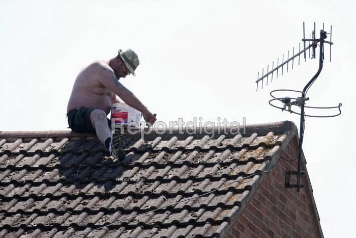 A man balancing on the apex of his roof sealing tiles with Grip It tile adhesive. Stratford-Upon-Avon, Warwickshire - John Harris - 2015-06-11