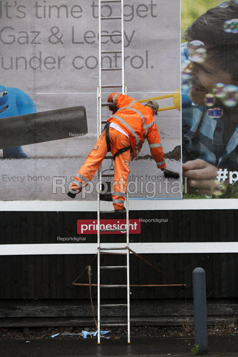 Worker pasting a new advertisement onto a billboard, Birmingham - John Harris - 2015-07-26