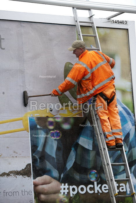 Worker pasting a new advertisement onto a billboard, Birmingham - John Harris - 2015-07-26