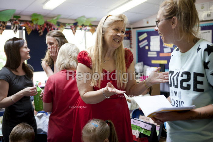 Head teacher talking to parent going through exercise books. Open Day for parents of pupils at primary school, St Richards First School, Evesham, Worcestershire - John Harris - 2015-07-06