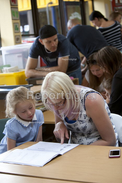 Parent going through exercise books. Open Day for parents of pupils at primary school, St Richards First School, Evesham, Worcestershire - John Harris - 2015-07-06