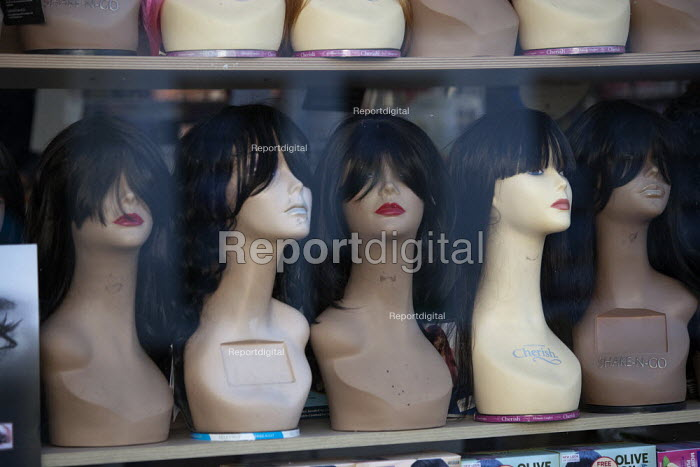 Hairpieces and wigs on wig stands in a shop window, Birmingham - John Harris - 2015-09-29