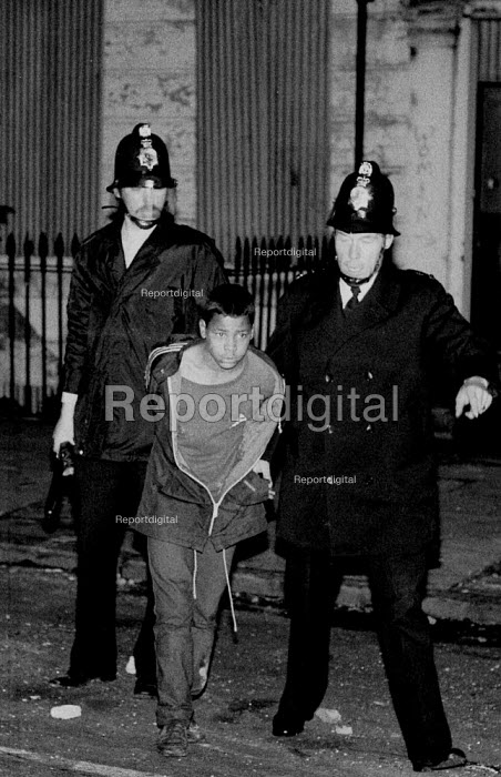 Police arrest a black youth during a weekend of some of the worst inner city urban riots in mainland Britain. Many accuse the police of racism. Toxteth riots, Liverpool 1981 - John Harris - 1981-07-06