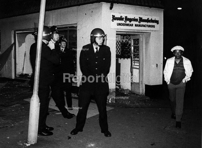 Police guard looted shop during riots in Handsworth Birmingham 1981. The predominantly black population has high unemployment, poverty and multiple deprivation. Many accuse the police of racism - John Harris - 1981-07-10