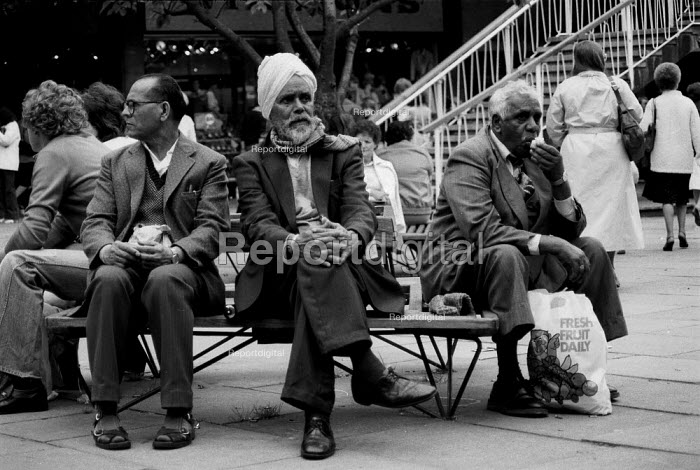 Asian men sitting in Coventry shopping precinct whilst skin heads with doc martin boots and union jack badges gather nearby. The recession in manufacturing intensifies and unemployed youth are targeted by right wing racist political parties 1982 - John Harris - 1982-03-30