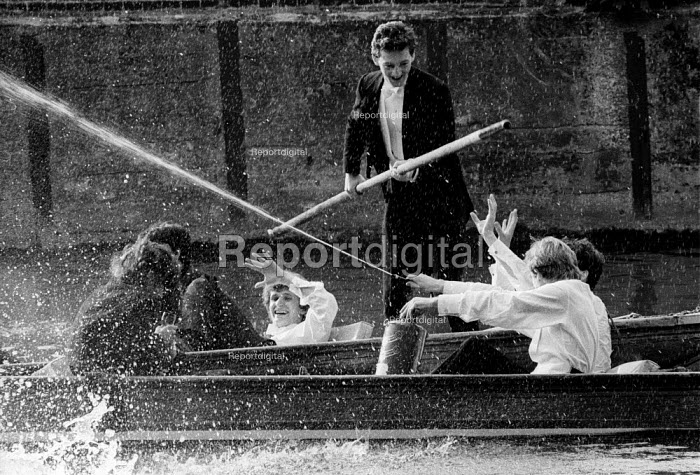Students punting down the river at dawn, splashing and letting off a fire extinguisher, May Balls Cambridge. ... - John Harris - 1983-05-04