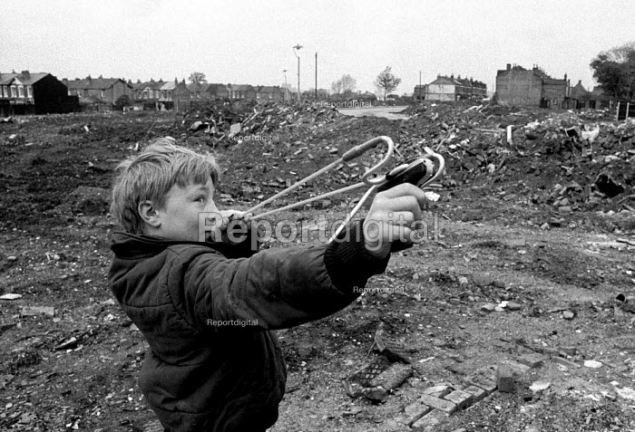 Youth firing catapult on waste ground whilst playing truant from school. Local authority Housing clearance area Birmingham - John Harris - 1983-04-01