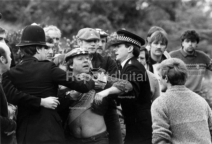Police hold back a striking miner as a working miner hurls abuse. Nottinghamshire Mansfield colliery 1984 - John Harris - 1984-04-24