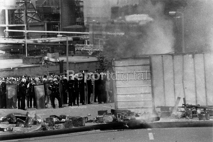 Police rest on their riot shields behind an overturned portacabin after charging into a mass picket of striking miners. Orgreave coke works Miner's strike South Yorkshire - John Harris - 1984-05-29