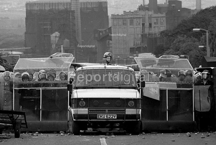 Police in riot gear & winged riot van confront a mass picket striking miners at the Orgreave coking works during the year long dispute n.r Sheffield 1984 - John Harris - 1984-06-18