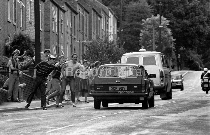 Striking miners and the community show their anger and bitterness as police escort a working miner - scab - through a pit village near Silverwood colliery South Yorkshire during the year long miner's strike. 1984 - John Harris - 1984-08-29