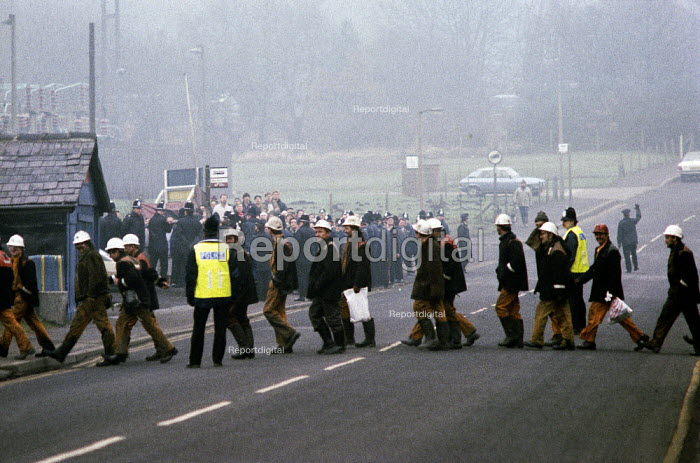 Picket of striking miners at Silverwood Colliery as working miners cross the road at the end of their shift. Miners strike South Yorkshire coalfield - John Harris - 1985-02-04