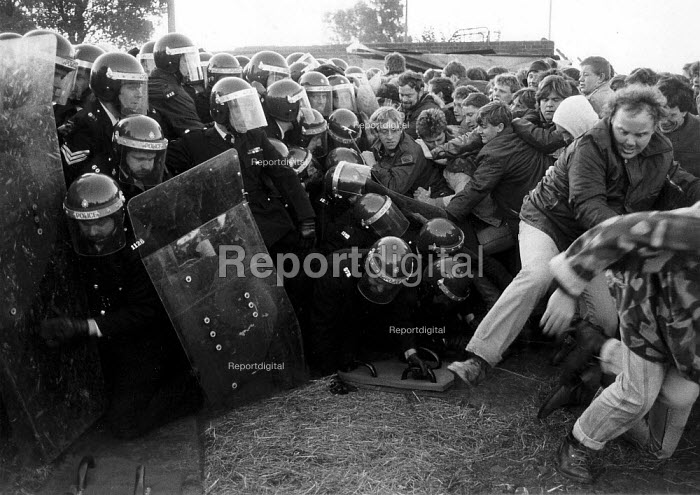 Striking miners pull line of riot police with long shields to the ground, Mass picket Kellingley colliery North Yorkshire. - John Harris - 1985-02-26