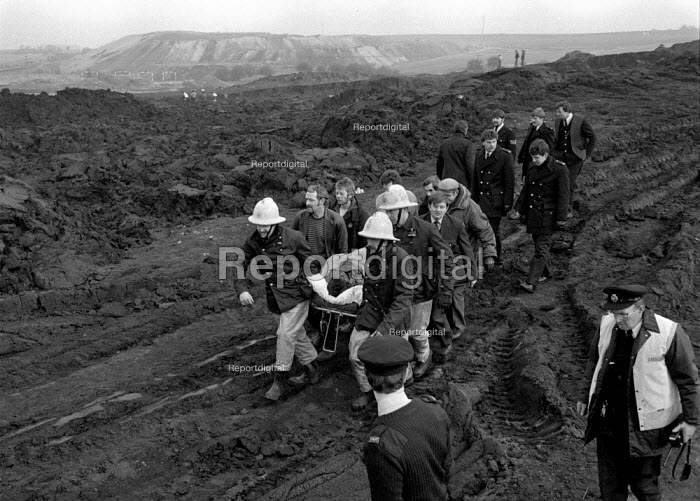 Emergency services rescue a miner buried alive whilst riddling for coal amongst the pit waste for fuel during the year long Miners strike. Silverwood colliery, Yorkshire - John Harris - 1985-02-18