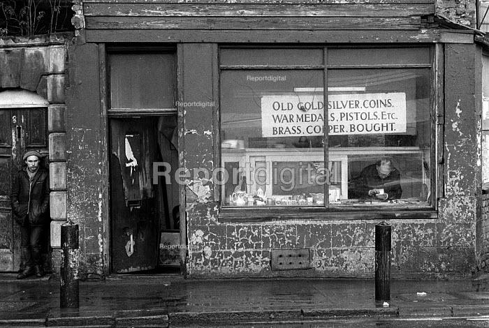 Unemployed man by pawnbrokers shop Tynebridge Newcastle upon Tyne 25.11.85 - John Harris