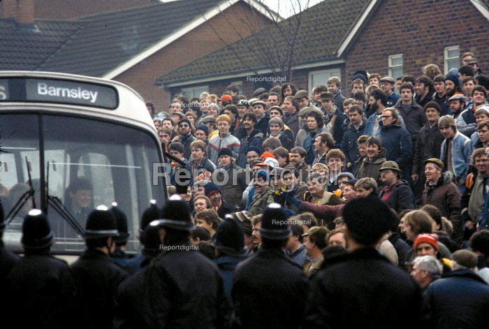 Good humour and laughter as a coach carrying working miners or scabs past police and a mass picket of Miners at Shirebrook Colliery, Derbyshire - John Harris - 1985-02-28