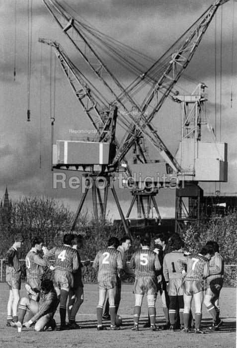 Shipyard football team training, 1986, Kvaerner Govan dockside cranes, Clydeside Glasgow - John Harris - 1986-05-18