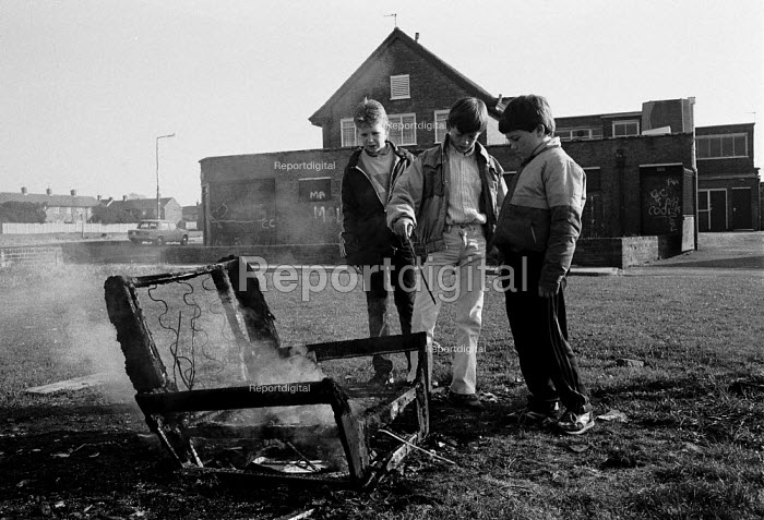 Youth burning an armchair in front of a boarded up pub on the Kirby housing estate, an area of high unemployment, poverty, multiple deprivation and dependency on welfare Liverpool 1986 - John Harris - 1986-11-03