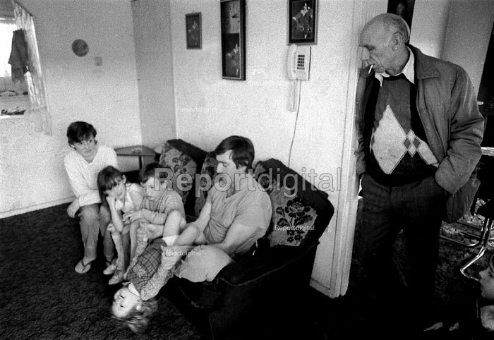 Mother Father children and grandfather at home in Kirby, an area of high unemployment, poverty, multiple deprivation, dependency on welfare and poor housing. Liverpool 1986 - John Harris - 1986-01-04