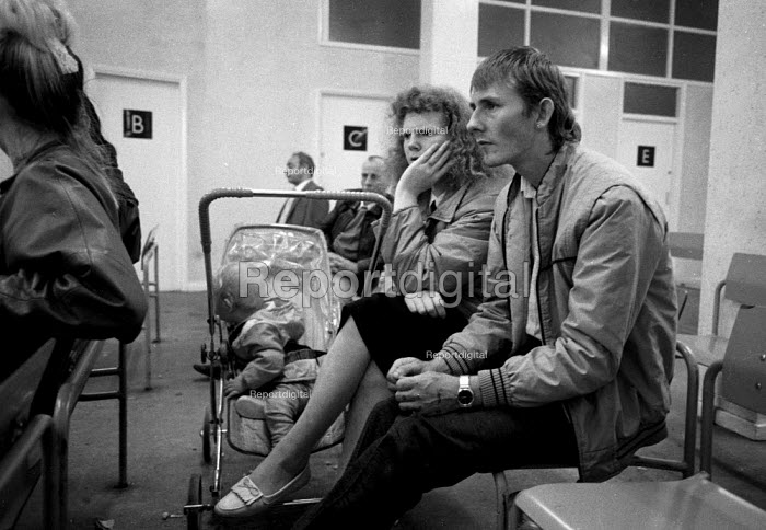 Unemployed parents with child waiting at a DHSS benefit office Coventry as the recession intensifies 1982 - John Harris - 1986-12-24