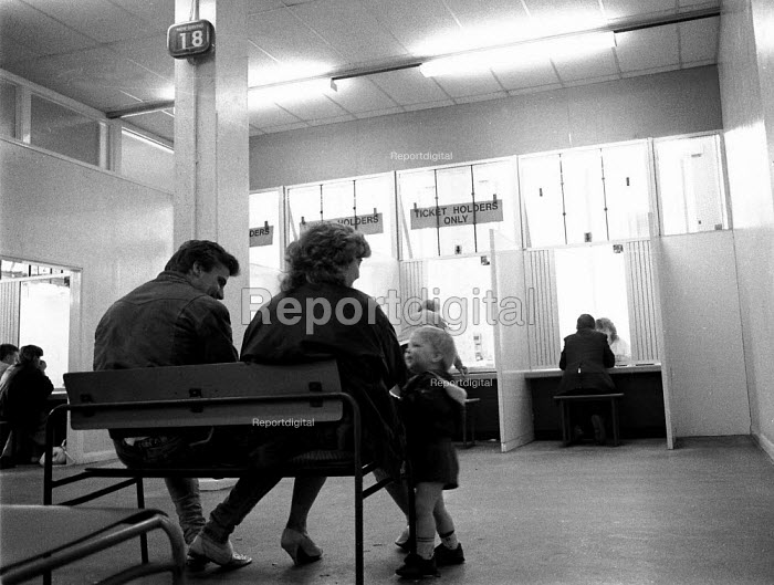 Unemployed parents with child waiting at a DHSS benefit office Coventry as the recession intensifies 1982 - John Harris - 1982-12-24