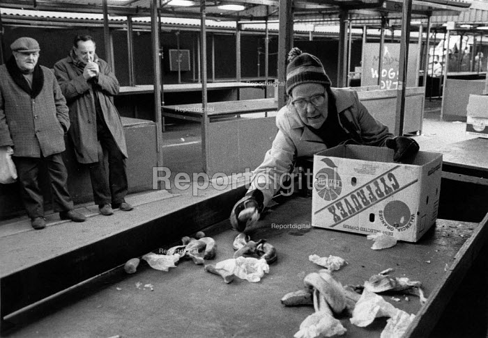 Pensioners and homeless mooching, trying to find edible food discarded by market traders at the end of the day to supplement their low income. The Bull Ring Shopping Centre Birmingham 1987 - John Harris - 1987-03-26