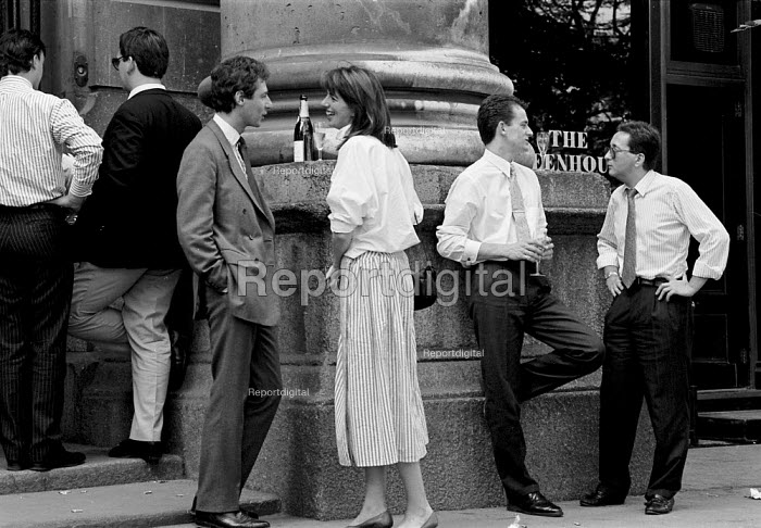 Young upwardly mobile city dealers - the symbol of the economic success of Thatcherism - relax with their champaign after a good days work in the finance capital. Yuppies were famous for their ability to make money fast in the deregulated money and financial markets of London 1987 - John Harris - 1987-06-09