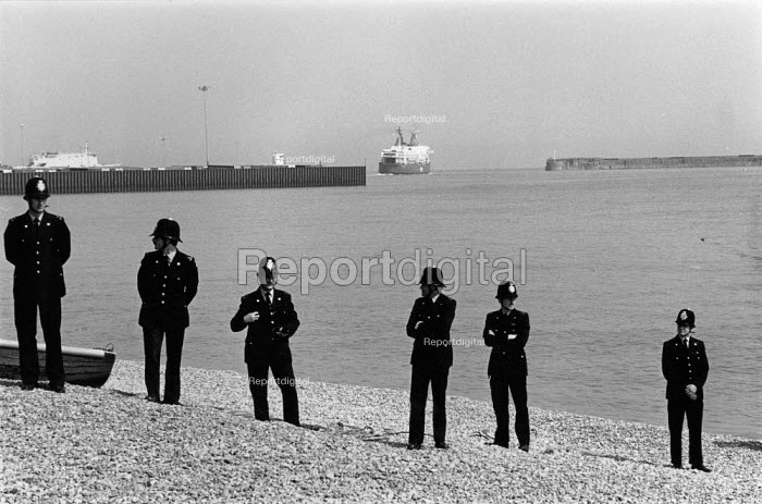 Dover NUS and P&O dispute. A ferry leaves the port and Police guard the seafront as Seafarers and their families show their anger at scab crew being bused into the port in an attempt at strike breaking. The P&O ferry company sacked the workers in an attempt to derecognise the National Union of Seamen - John Harris - 1988-05-12