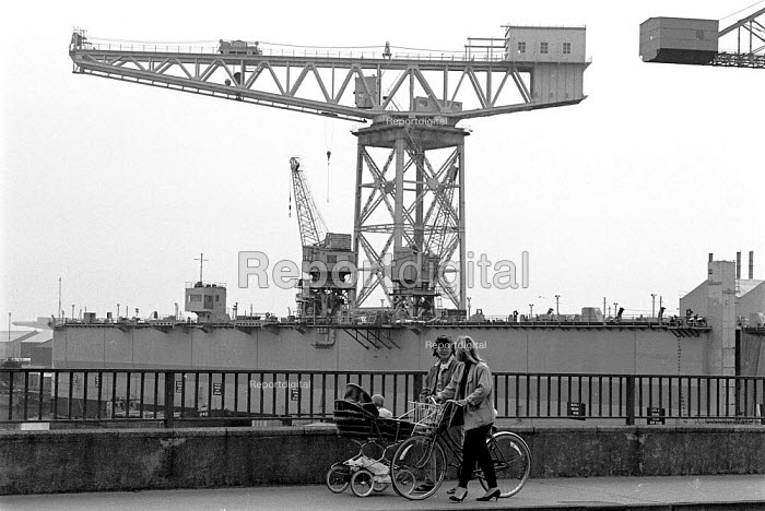 Women with push chair and bicycle walking past the VSEL shipyard which builds the Trident nuclear submarine in the background. Barrow in Furness - John Harris - 1988-06-16