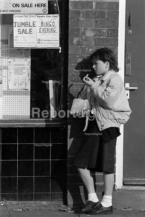 School pupil eating a bag of chips for lunch in the street as the price of a school meal doubles. Bradford - John Harris - 1988-11-04