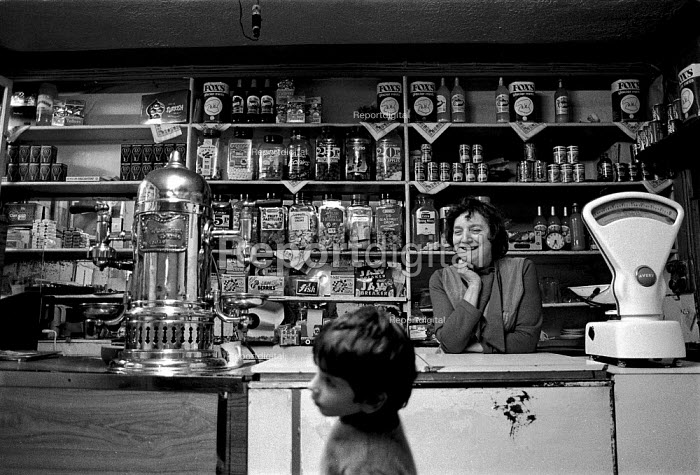 Proprietor and child buying sweets in a local Italian corner shop and cafe, Penrhiwceiber, Cynon valley an area of low family income, poor housing and deprivation. South Wales 1989 - John Harris - 1989-02-21