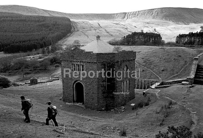 Walkers pass pumping station on the edge of a reservoir - John Harris - 1989-02-21