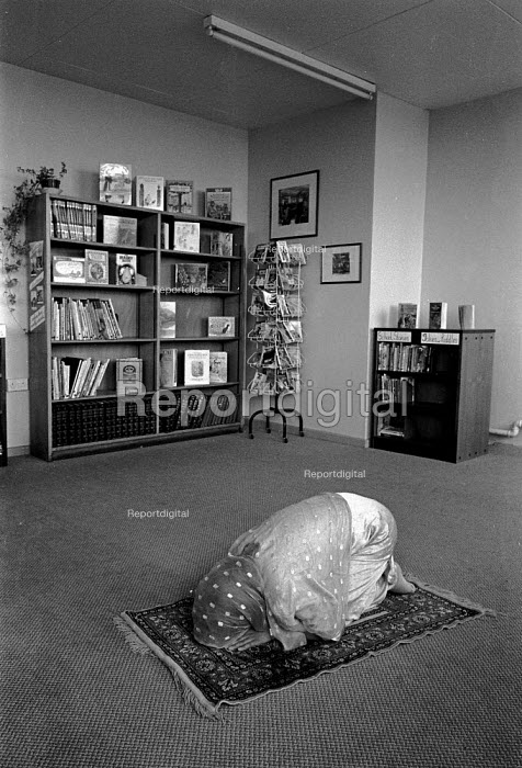 Muslim pupil praying in a quiet area set aside for worship in the library of a secondary school in Dewsbury Yorkshire - John Harris - 1989-05-09