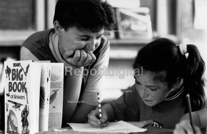 Teacher helping pupil with writing English lesson at a Primary School - John Harris - 1989-06-16