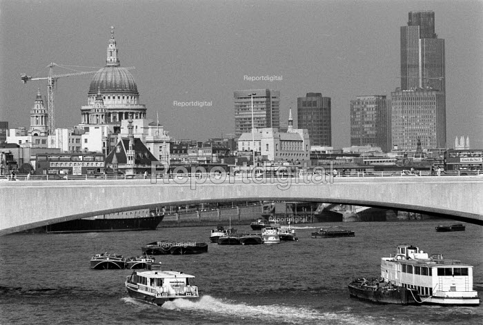 River bus full of commuters goes under a bridge over the Thames. St Pauls and the City of London are in the background - John Harris - 1989-07-12