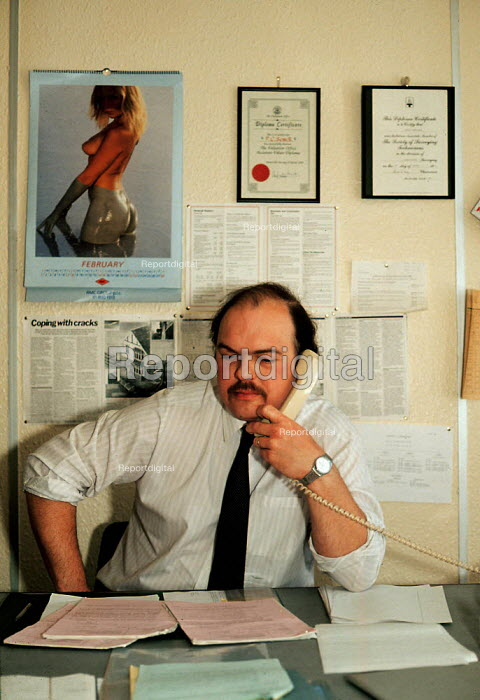 Inland Revenue Tax collector making a telephone call. Many find pin up calendars featuring so called glamour photographs of women sexist and offensive and argue that such material is inappropriate for an office environment. - John Harris - 1990-02-20