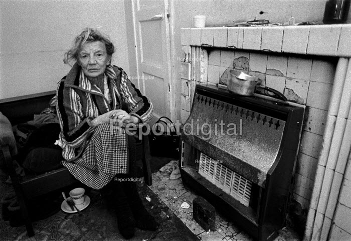 Old age pensioner trying to keep warm during very cold weather. Every winter 30,000 - 60,000 people in the UK die of cold related illnesses - avoidable deaths caused by poor housing and low incomes. People on the lowest incomes and benefits can least afford high heating cost, but they occupy the least energy efficient homes and have high heating needs. - John Harris - 1991-01-18
