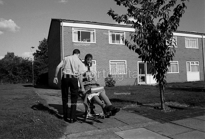 Ambulance crew help an elderly disabled out patient to her ground floor flat - John Harris - 1991-05-10