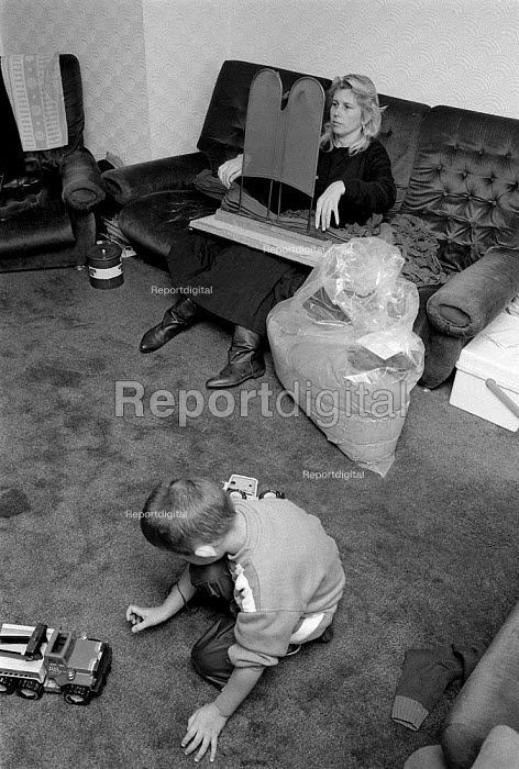 Women homeworker checking and packing tights for low pay whilst her child plays Leicester 14/11/91 - John Harris - 1991-11-14