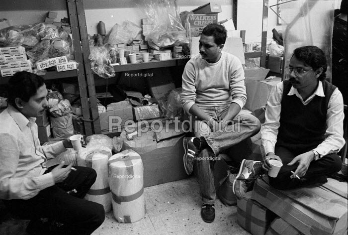 Asian men taking a break from work in a Leicester sweatshop producing textiles. The workers have low pay and poor conditions - John Harris - 1993-04-21