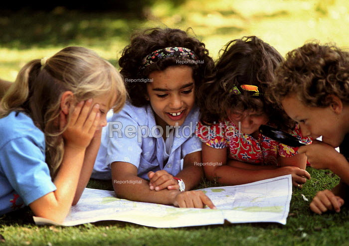 Junior and Primary School pupils looking at map of the area in a city park, geography lesson. London - John Harris - 1993-07-09