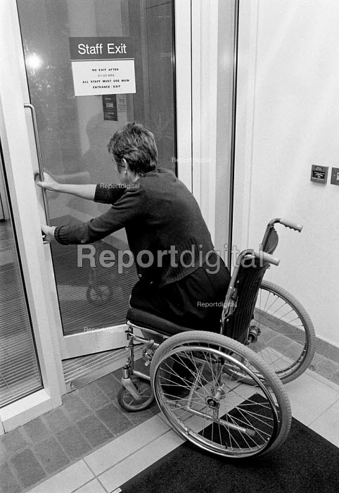 Disabled office worker getting access to her work place. The building has been designed for wheelchair access - John Harris - 1993-11-09