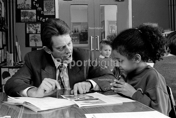 OFSTED - Office For Standards in Education inspector inspecting at a midlands Junior school. Working with a pupil - John Harris - 1993-11-18