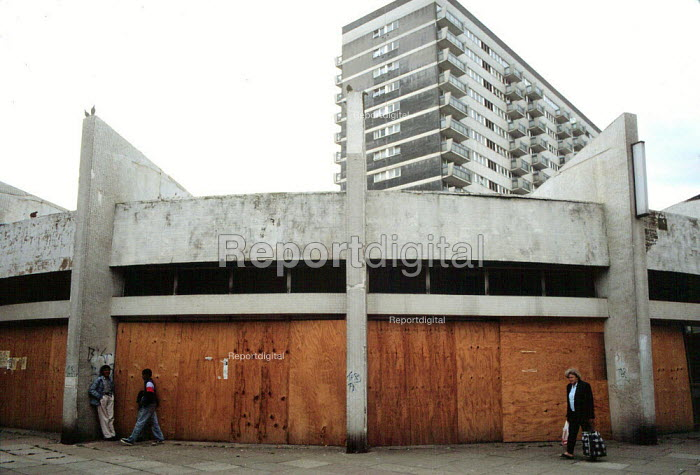 Newtown shopping precinct where most businesses have closed and High rise housing on an inner city estate Birmingham, an area of multiple deprivation, high unemployment, high crime rate, dependency on welfare and low incomes - John Harris - 1994-04-23
