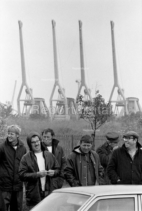 Striking dockers picketing in the rain King George Dock Hull 1984. The strike was called by the TGWUs national docks committee after British Steel had used workers who were not registered dockers to unload iron ore at Immingham dock on the Humber. The ore was for Scunthorpe steelworks. - John Harris - 1984-07-10